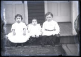 Three siblings seated on porch step