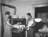 Family in a kitchen, a photograph from the Lucas Metropolitan Housing Authority, 1940